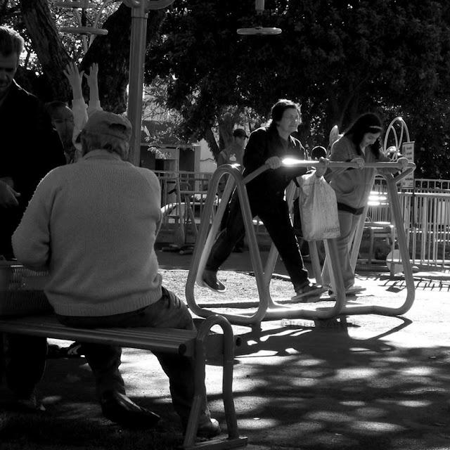 Fotografia P e B. Praça ensolarada. Sombra das árvores refletem no chão. Pessoas com agasalhos de frio. À direita, pouco distanciadas, juntas, mulher idosa e menina em pé num equipamento de metal tubular, movimentam pernas em vai e vêm, pés sobre pedais,seguram-se no tubo a frente do corpo. A mulher, séria, de óculos, cabelo curto, apoia sacola no braço esquerdo, olha para frente. Menina sorri olhando para os pés, cabelos longos, pretos. À esquerda, 2 homens idosos, 1 em pé, outro de costas sentado no banco.