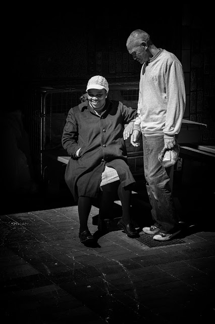A man and a woman touch hands in the sunshine off St George's Mall Cape Town.
