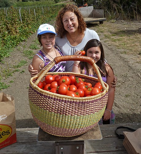 mother and two daughters with giant basket of tomatoes on scale