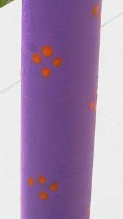 Szöveg: Stilizált virágminta a csövön. Kép: A roller lilára festett csövén narancssárga színű, apró stilizált virágmintákat rajzoltam. A virágminta szirma egy-egy pötty, amit rombusz alakban pöttyintettem a csőre.