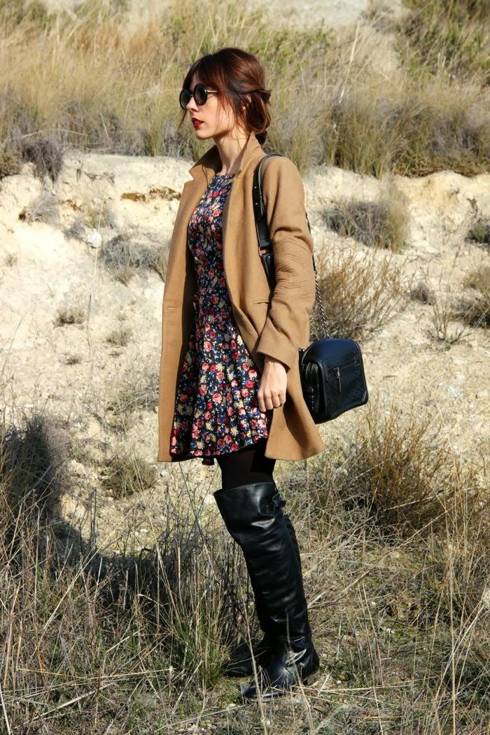 abrigo camel, vestido flores, bandolera negra, gafas pasta y botas mosqueteras