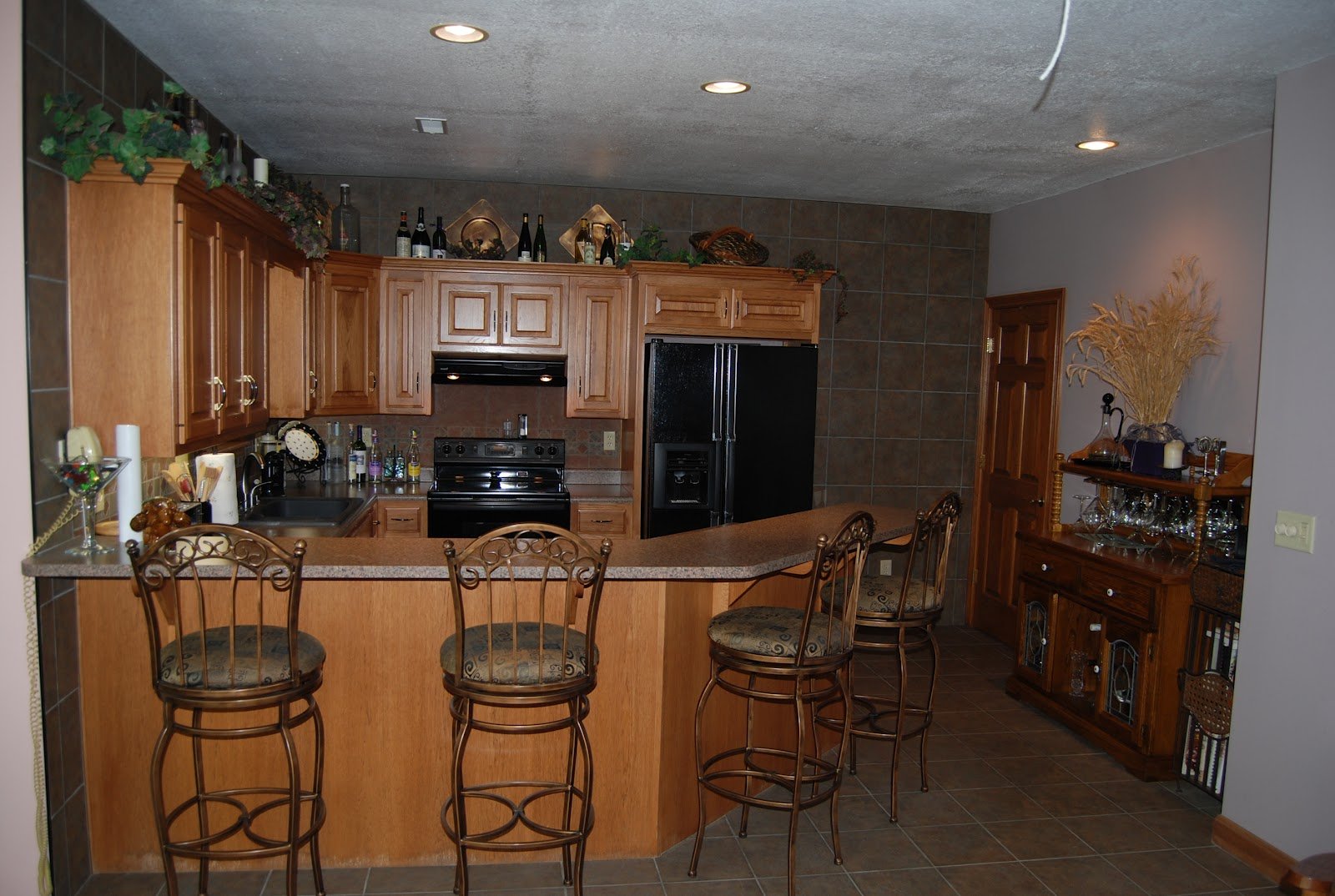 full kitchen with lots of beautiful cabinets and tile accents