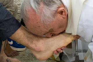 Pope Francis I kisses the feet of a young offender at the Casal del Marmo youth prison outside Rome. Humble Pope snubs traditional celebration at city center Basilica.