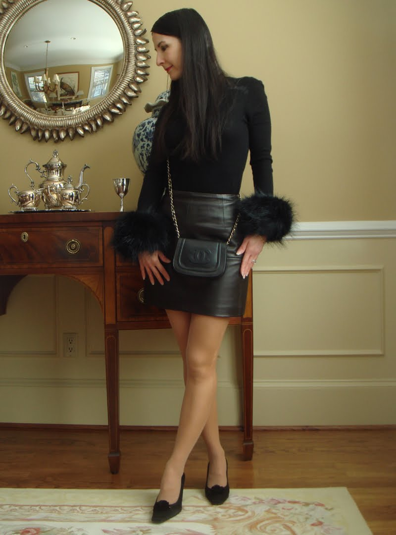 Full body outfit of black turtleneck with faux fur cuffs.