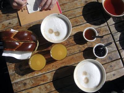 Frühstückstisch aus der Vogelperspektive: Milchkaffee, Orangensaft, Zopf und Konfitüre