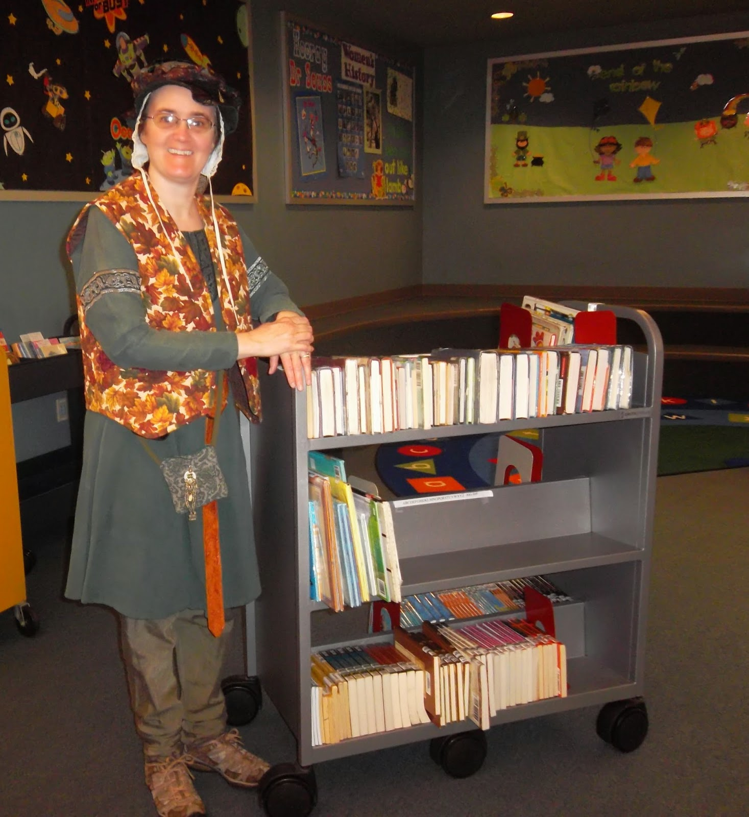 "Cynthia Parkhill wearing brown-leaf vest over medieval-style tunic and trowsers with a brown and green Tudor ""flat cap"" over white-linen coif, standing next to library shelving cart filled with books"