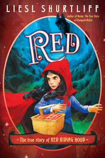 Book cover: Red, the True Story of Red Riding Hood, by Liesl Shurtliff. Image depicts a young girl wearing a blue dress and red hooded cape. Her black hair blows free from beneath the hood of her cape. In the background is a wooded scene with a wolf peering at her from around the back of a tree trunk