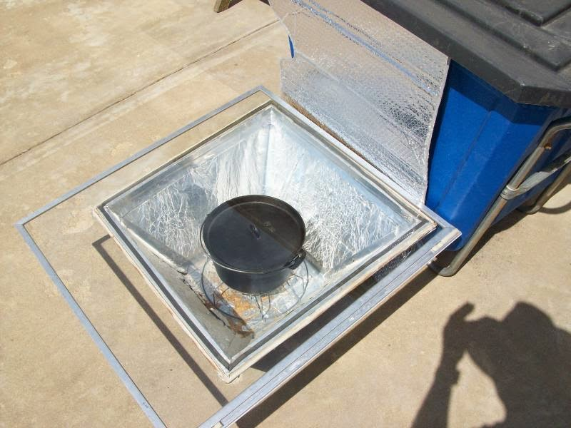 Solar oven made with a box, aluminum foil, old window, black  pot with clear lid, and rack