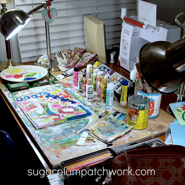 desk with colorful paints and art supplies
