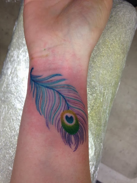 Peacock feather tattoos on man wrist
