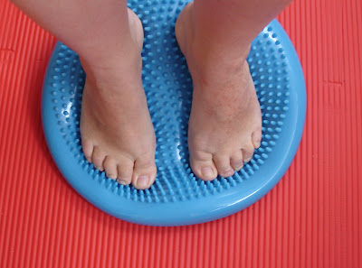 closeup of feet standing on a pilates balance pad