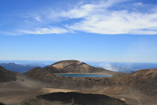 Blue lakes in a red volcanic crater under a blue sky.