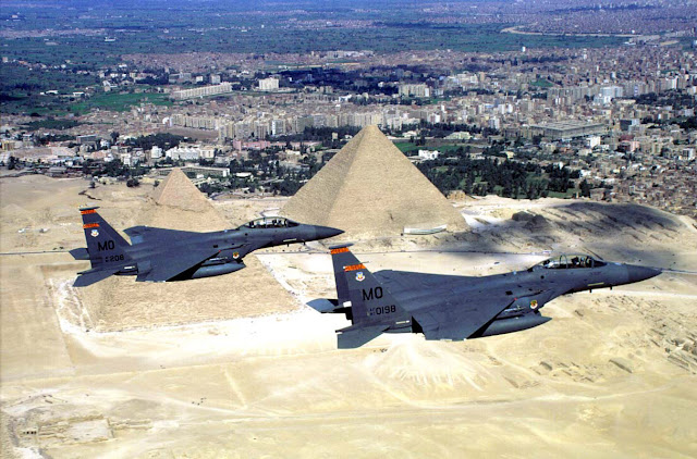 A pair of F-15E Strike Eagles, fly over the pyramids.