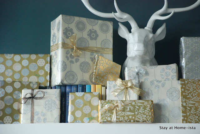 silver and gold gifts on a mantle with a deer head