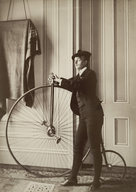 Frances Benjamin Johnston, full-length self-portrait dressed as a man with false moustache, posed with penny-farthing bicycle, facing left. Between 1880 and 1900.