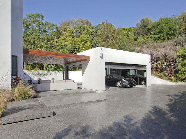 Photo of garage with the car connected to the house with terrace