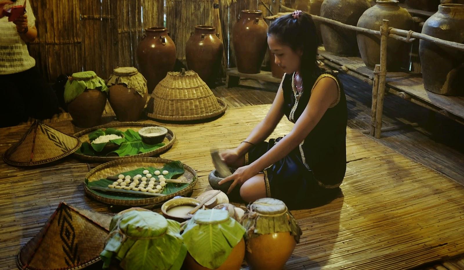 A young Dusun maiden preparing rice wine at Mari Mari Cultural Village