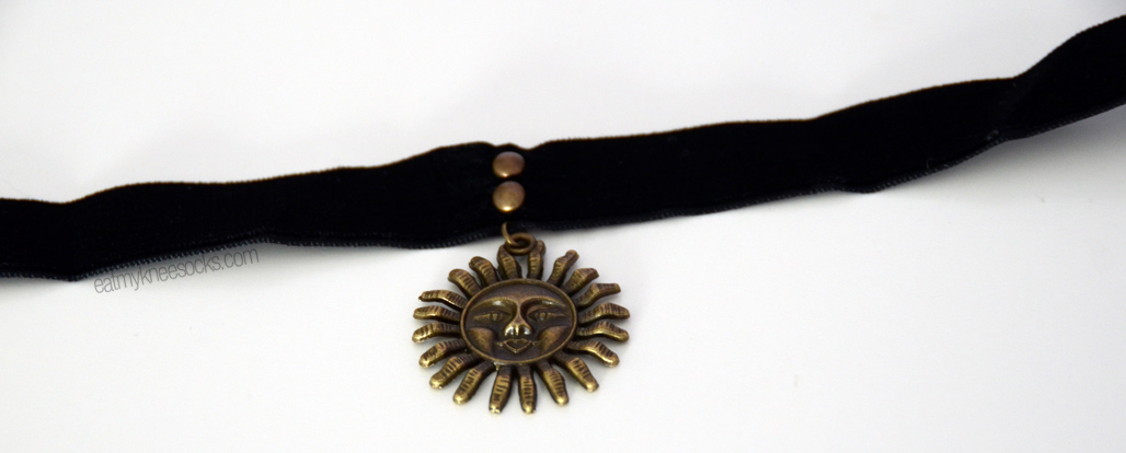 Closeup of the bronze sun details on the black velvet choker from Born Pretty Store.