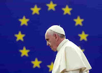 A photo courtesy of the European Commission of Pope Francis passing by the EU emblem and his body is nearly centered within the EU flag of 12 yellow stars against a blue background while attending and speaking at an  EU Parliament Plenary Session