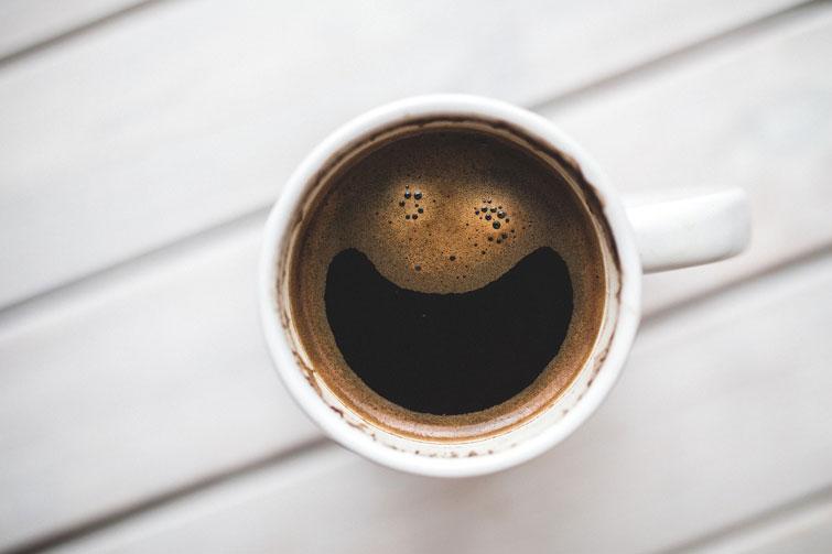 Taza de café sonriendo en la oficina