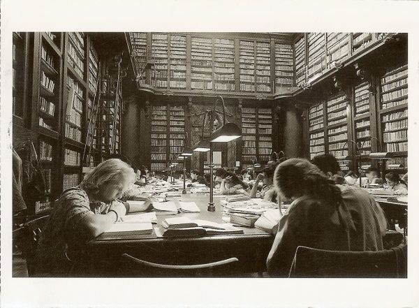 black and white postcard of people working and studying in an ancient library