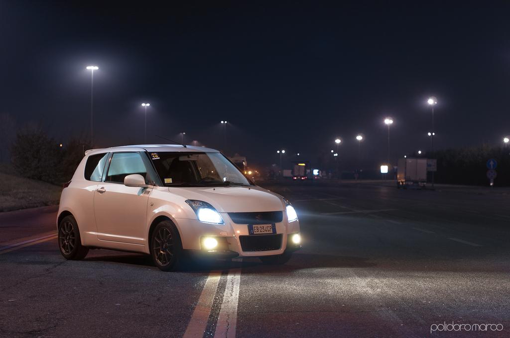 Suzuki Swift IV. Znany japoński hatchback, z napędem na przód. Świstak. Zdjęcia samochodów w nocy.