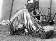 Interior of tepee, man kneeling on ground removing buffalo hide around skull .