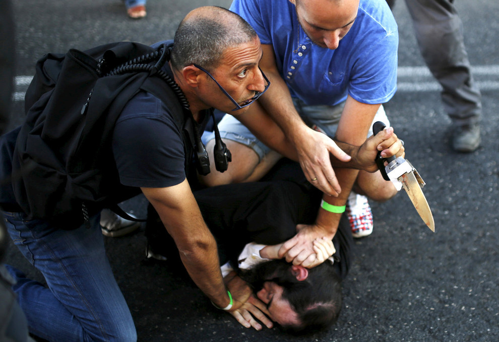 70 Of The Most Touching Photos Taken In 2015 - People disarm an Orthodox Jewish assailant after he stabbed and injured six participants at an annual gay pride parade in Jerusalem.