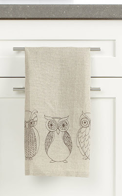 linen dishcloth with owl theme hanging on a cupboard handle