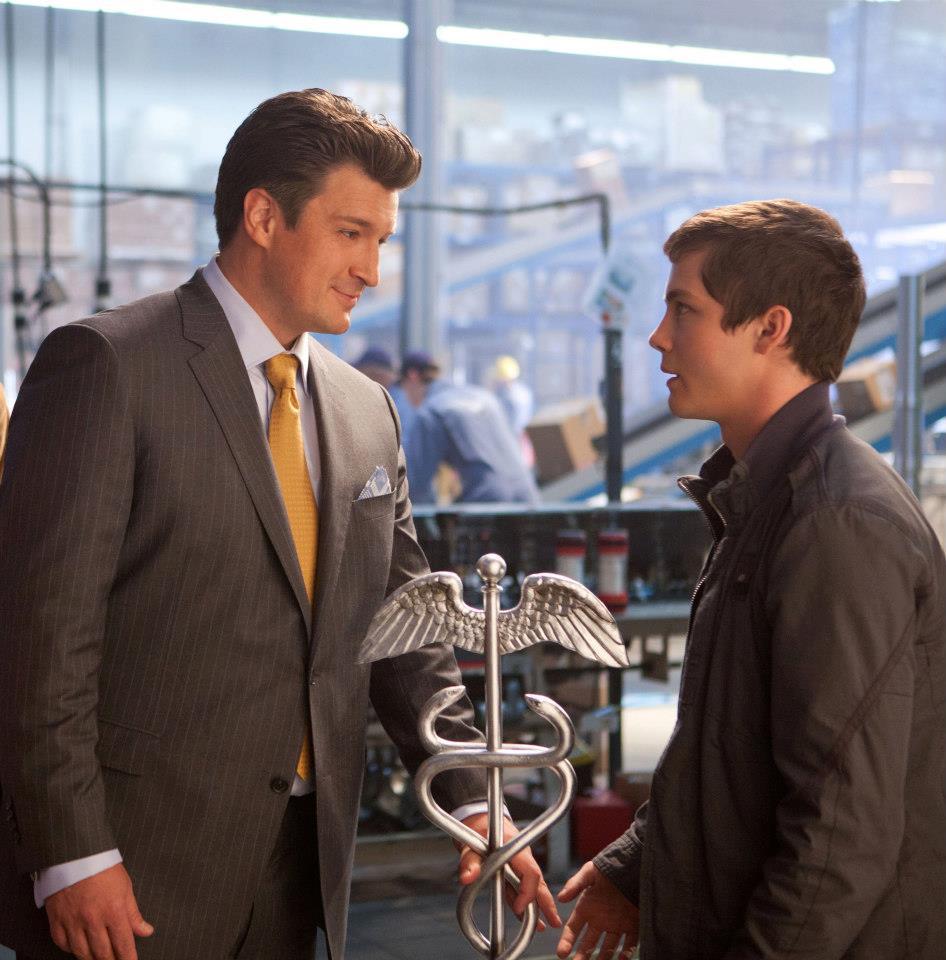 Nathan Fillion (Hermes) y Logan Lerman (Percy) en en una imagen oficial de la película El Mar de los Monstruos. Están hablando y entre ellos está el caduceo del dios (con las serpientes Martha y George).