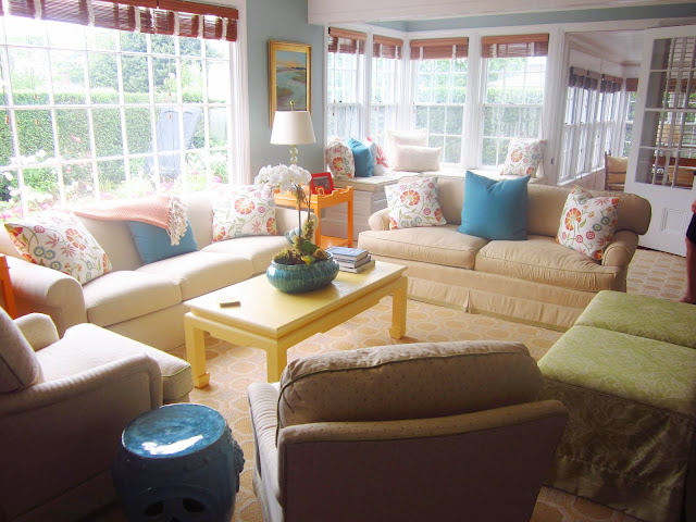 living room with paned windows with bamboo shades, two neutral sofas with blue and flower printed accent pillows, a yellow coffee table and three armchairs.