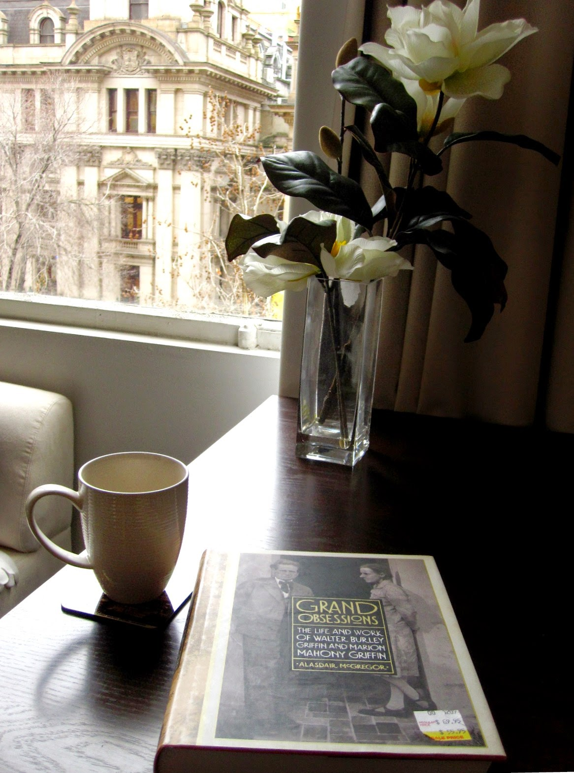 Table with a vase of magnolias, a mug and a book on it. The window behind overlooks an old Melbourne building on Swanston Street..