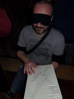 Ο Βασίλης Μαντζοράκης με μάσκα διαβάζει ανάγλυφο χάρτη του μετρό