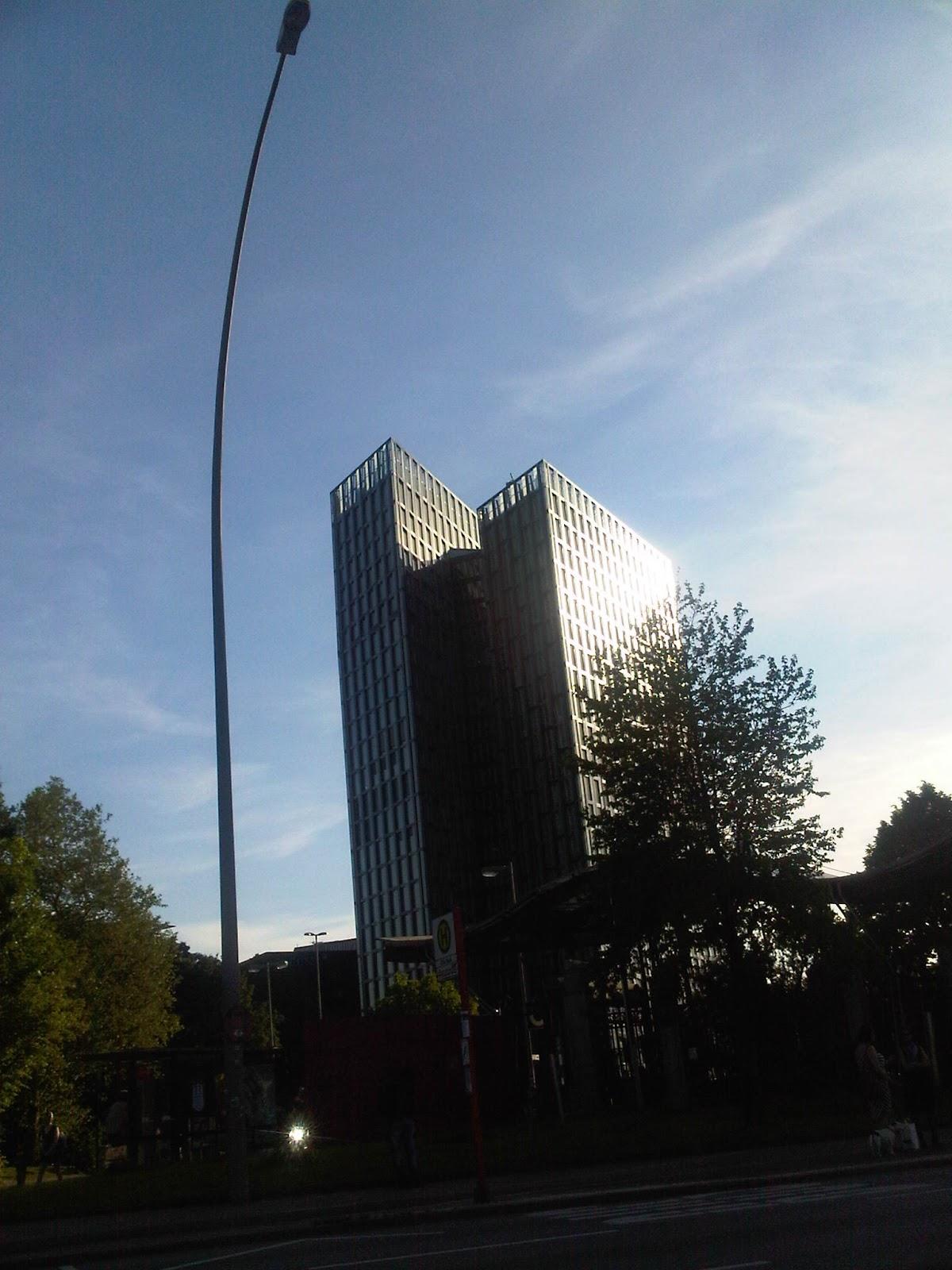 Tanzende Türme auf St. Pauli von der Straße Millerntorplatz aus. Blauer Himmel, Wolken, Sonnenreflexion auf den Scheiben. Baum vor den Tanzenden Türmen.