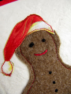 Santa hat appliqued to felt Gingerbread man