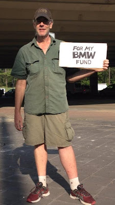 Panhandler with sign for BMW fund