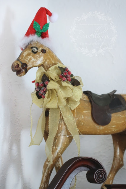 Primitive pull toy horse decorated for Christmas with hat and berry ribbon.