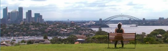 Misaki sits on a park bench overlooking the cityscape and Sydney Harbor Bridge.