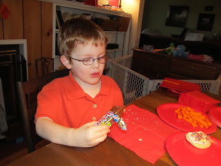 Little Mister in an orange shirt, eating a Three Musketeers bar