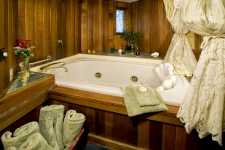 Jacuzzi tub for 2 surrounded by wood skirting, bubble bath fluffy towels