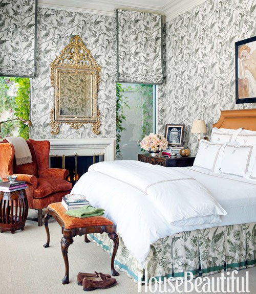 bedroom with walls covered in grey and white silk fabric, orange arm chair, fireplace with a large mirror hanging above it, ottoman at the foot of the bed with a wooden headboard