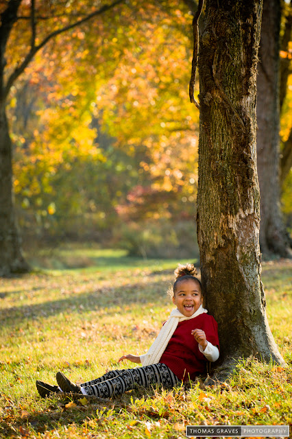 This young lady plays hide and seek behind a tree on a pretty fall afternoon.