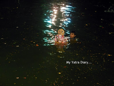Ganesh Visarjan taking place in an artificial lake in Mumbai
