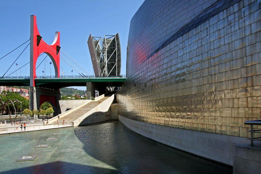 Foto na zona do lago, em primeiro plano, a parede metálica do museu à direita e ao fundo a ponte
