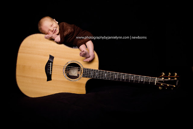 newborn baby boy wrapped with big grin sitting on top of guitar