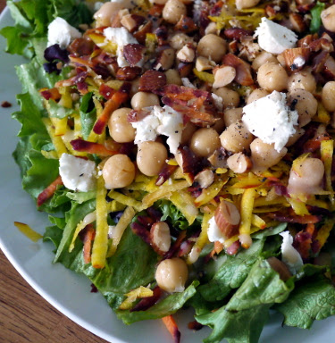 Spring salad with greens, shredded root veg, chickpeas, goat cheese, and almonds