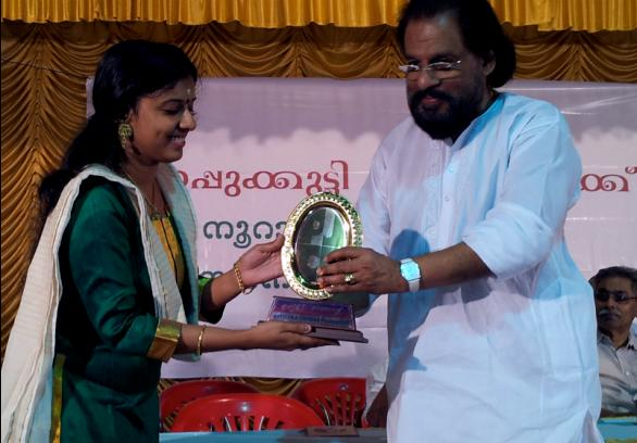 Sithara Krishnakumar receiving award from Yesudas