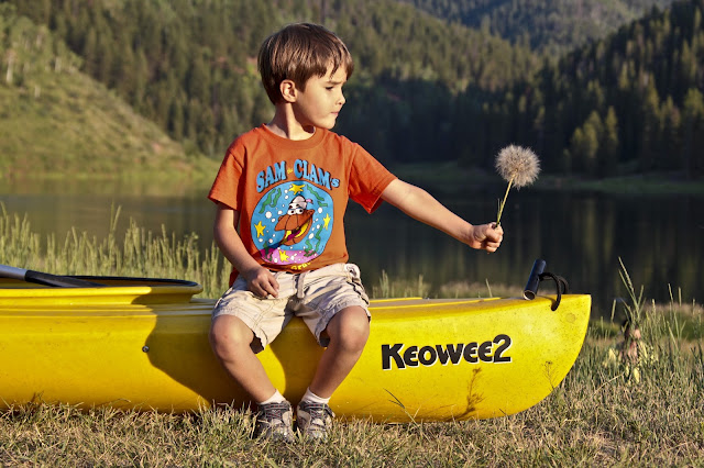 A boy holding a baseball sized dandelion and sitting on a kayak at Sylvan Lake State Park near Eagle, Colorado.