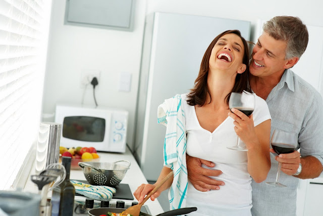 Middle-aged couple laughing and embracing in the kitchen.