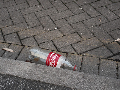 Coca-Cola tin in gutter